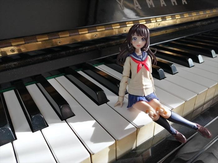 ピアノの鍵盤の上に座った結城まどか